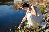 stock photo of fancy-dress  - Young woman sitting by water and looking at her reflection - JPG