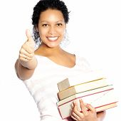 stock photo of librarian  - Beautiful smiling vivacious African American woman carrying a pile of textbooks giving a thumbs up of approval and success isolated on white - JPG