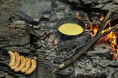picture of smut  - Fried eggs on fire at iron fried pan with grilled sausages on skewer - JPG