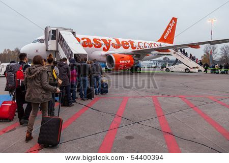 People Walking In A Runway To Enter An Easyjet Plane