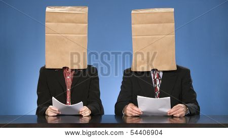 Newscasters sitting doing the news with paper bags over their heads.