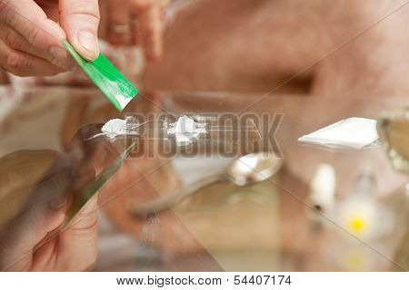 Closeup of person making lines of cocaine.  Shallow depth of field.  **Dramatization - no illegal drugs were used in the making of this photograph**