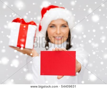 christmas, x-mas, valentine's day, celebration concept - smiling woman in santa helper hat with gift box and postcard