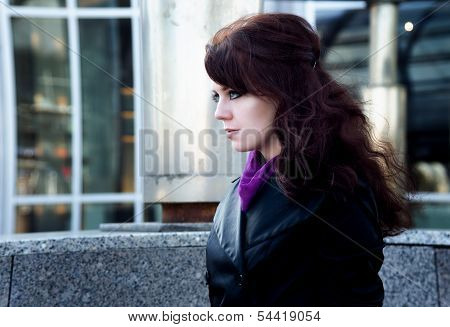 Beauty portrait of young woman with black eyeliner on urban background