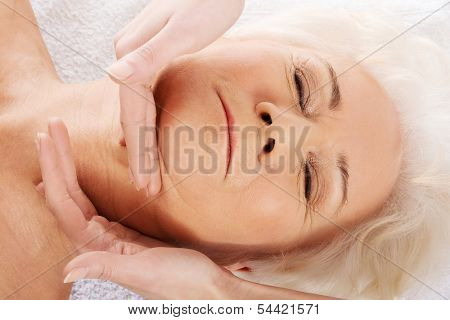 An old woman is having a face massgae. Spa concept. Over white.