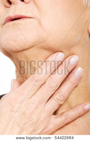 Close up on older woman's hand holding neck. Body part.