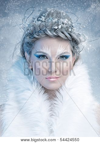 Ice queen - beautiful woman in winter professional makeup with white fur