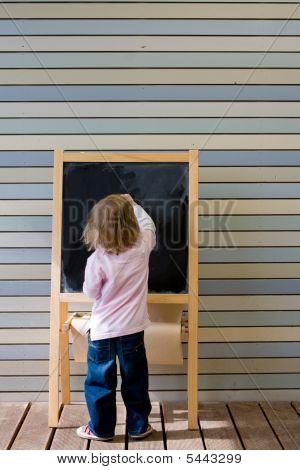 Cute Young Caucasian Boy Writing On A Blackboard