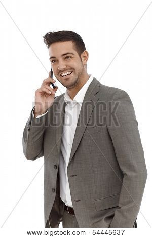 Happy young businessman talking on mobile phone over white background.