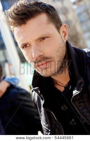 Closeup portrait of goodlooking young man in black, outdoors.