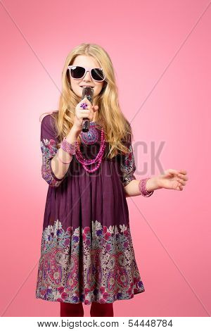 Beautiful ten years girl singing into the microphone. Over pink background.