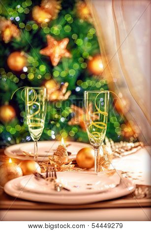 Christmas table setting, festive dinner still life and beautiful decorated Xmas tree at home, New Year eve, luxury wintertime party concept