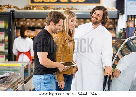 Happy worker assisting couple in buying meat at butcher's shop