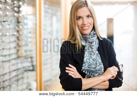 Portrait of happy woman holding glasses in optician store