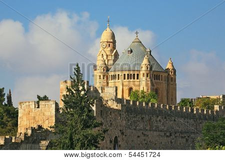 The Catholic Church of Dormition in Jerusalem. The morning sun illuminates the dome and the tower of the abbey. Battlements of Jerusalem surrounded by majestic building