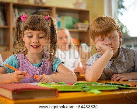 Little girl in a school with sleepy redhead classmate