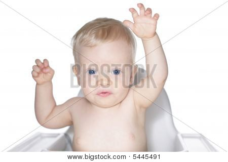 Baby In High Chair With Hands In The Air