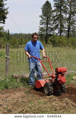 Man Rototilling Garden.