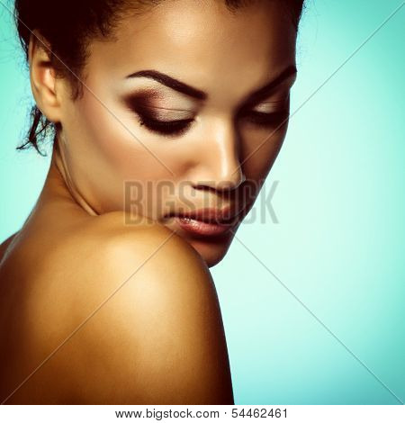 Young mulatto fresh woman with beautiful makeup, over blue