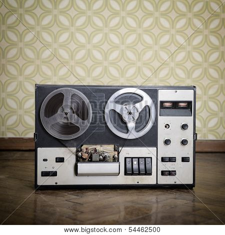 Old portable reel to reel tube tape-recorder is on obsolete parquet in retro room with vintage wallpaper. Toned