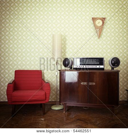 Vintage room with wallpaper, old fashioned armchair, retro player, loudspeakers, clocks and standart lamp, toned