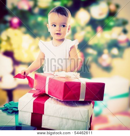 Holidays, baby girl opening box with presents, christmas, birthday, new year, x-mas concept - happy child girl with gift boxes