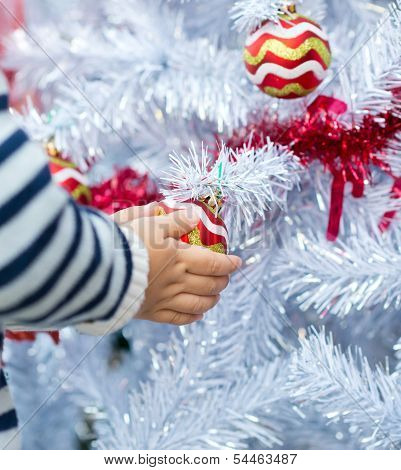 Child holds a Christmas red balls