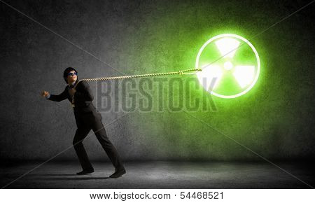 Young man wearing goggles pulling radioactivity symbol with rope
