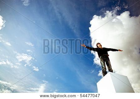 Teenager with his arms wide open looking into a blue sky
