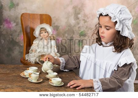 Sweet victorian girl posing in the old style with an antique teapot