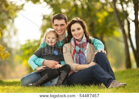 Happy family, mother, father and daughter in the park
