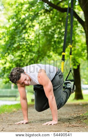 Young man exercising with suspension trainer sling in City Park under summer trees for sport fitness