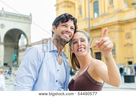 Man and woman or young couple making trip as tourists in Munich at the Odeon Church with city map on the tablet computer