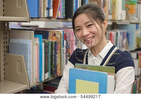 Young Student Holding Books Near Bookshelf