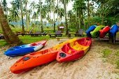 stock photo of kayak  - Colorful Kayaks are Heap on the beach - JPG