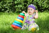 stock photo of human pyramid  - Smiling little girl playing with colorful pyramid on the grass in the park - JPG