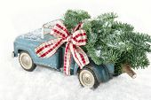 pic of blue spruce  - Old blue toy truck carrying a green Christmas tree covered with snow and a red ribbon on white snowy bakcground