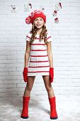 stock photo of  preteen girls  - Little fashion girl in fashion Christmas clothes posing over white brick background - JPG