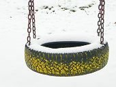 stock photo of tire swing  - snowy tire swing on the empty playground in winter - JPG