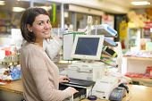 stock photo of cash  - Young woman at cash register in a store - JPG