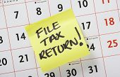 image of self assessment  - Hand written reminder to File Tax Return on a yellow Post it Note stuck to a calendar background - JPG