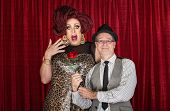 stock photo of drag-queen  - Retro man giving surprised drag queen a rose - JPG