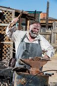 image of anvil  - Old West Blacksmith Swings Hammer at an Anvil - JPG