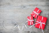 stock photo of gift wrapped  - Gift boxes with bow on wooden background - JPG