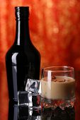 image of bailey  - Baileys liqueur in bottle and glass on red background - JPG
