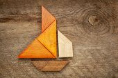 image of tangram  - abstract picture of a sailing boat built from seven tangram wooden pieces over a rustic  barn wood - JPG