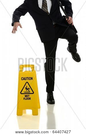 Businessman slipping on wet floor in front of caution sign isolated over white background