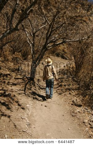 A Man With A Hat Walking Up The Hillside In Mexican Desert