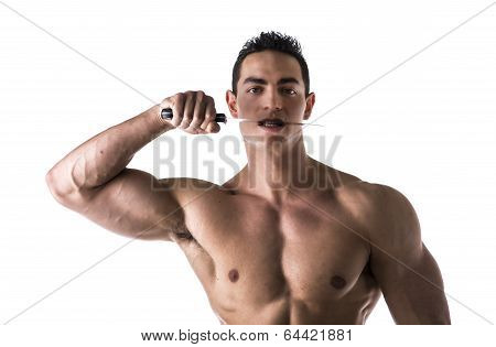 Muscular Young Man Biting Knife