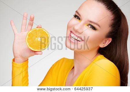 Young brunette with orange in her hand